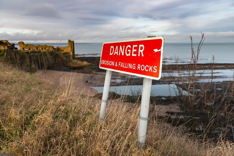 """warning sign reads #2Danger: erosion and falling rocks"""". St ANdrews Castle is visible in the background"""