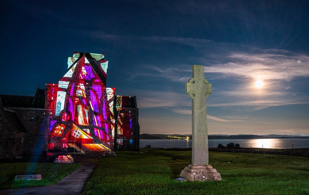A colourful projection illuminating the wall of an abbey