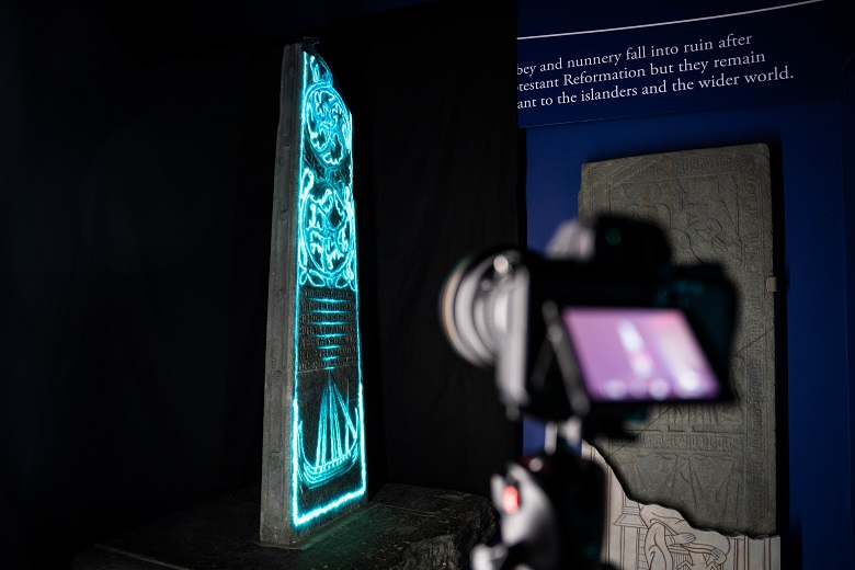 The view from behind a camera capturing images of a projection onto a carved standing stone
