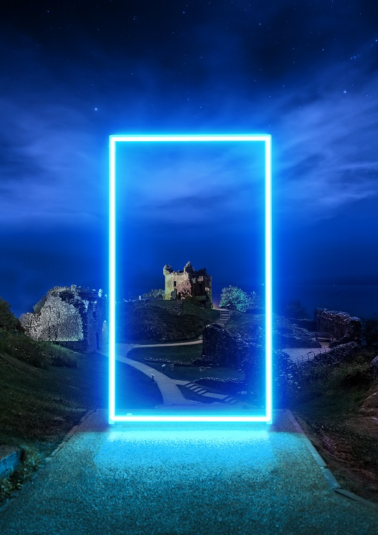 The ruins of a castle at night, framed by a dazzling bright blue projection