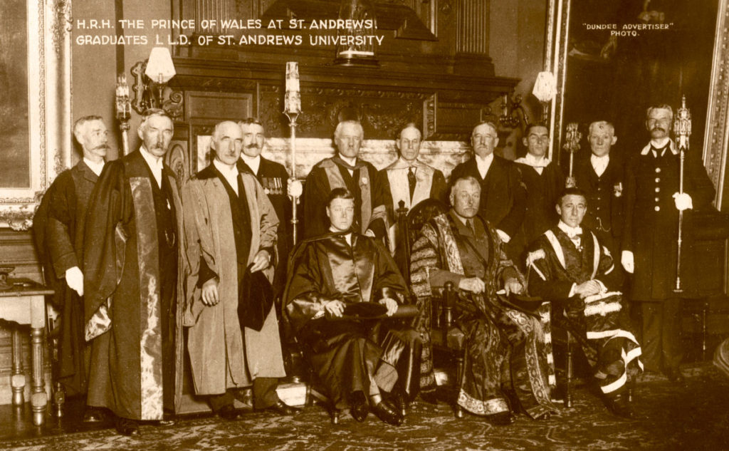 A group of robed, moustached men surrounding the young Prince of Wales in a grand hall